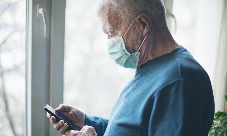 Man wearing surgical mask and looking at phone