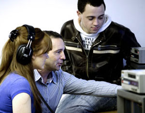 Image: two students learning journalism skills from tutor