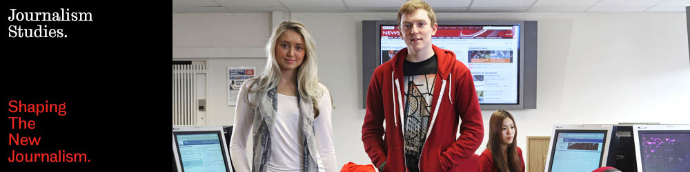 Image: three students in the broadcast newsroom