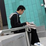 A student reading on the steps of the IC