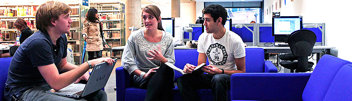 Students in a library discussing work together, with a laptop