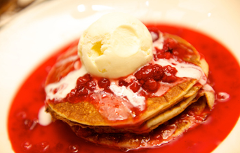 A pancake topped with berries and ice cream