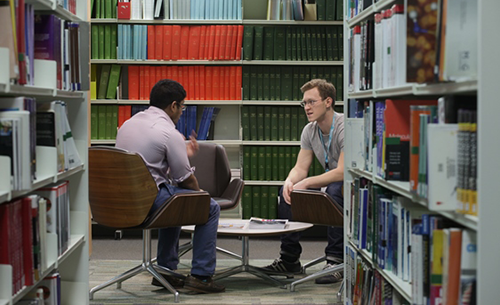 two men sat at a table between library shelves
