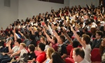 Maths Inspiration event with students holding up hands in lecture theatre