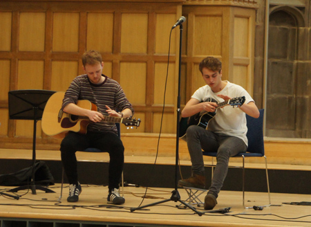 Two students playing guitar on stage