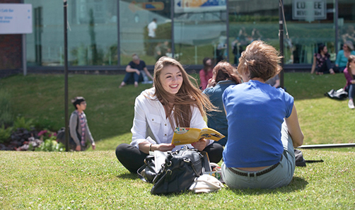 Photo of two student sitting on the grass outside the Students' Union