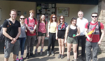 Students and staff at busstop after walking in the Peak District