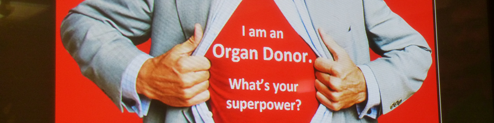 "A person opening their shirt to reveal tshirt reading: ""I'm an organ donor. What's your superpower?"""