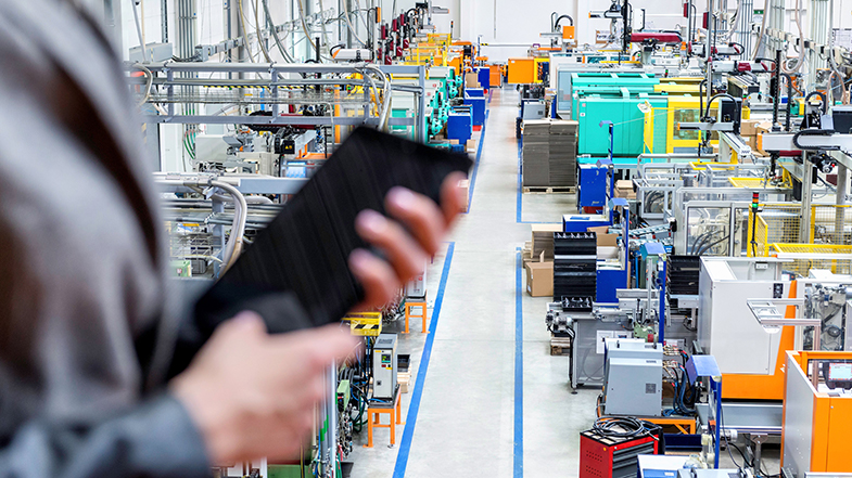 Person holding tablet in factory