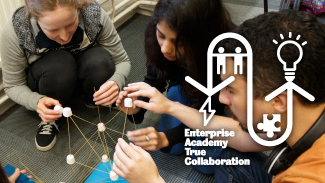 A group of students building a tower from dried spaghetti, on which marshmallows are balanced