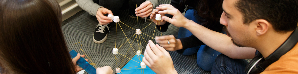 Group of students building a tower with dried spaghetti and marshmallows