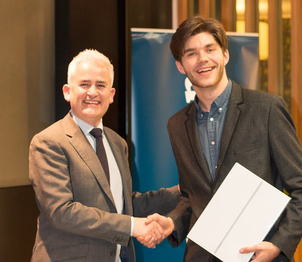 Liam Mullen receives first prize – an iPad pro – from Philip Hoare, managing director of Atkins. Pho