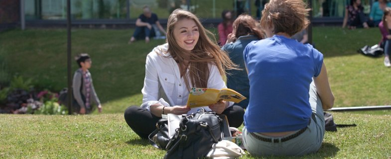Students sat on grass at Open Day