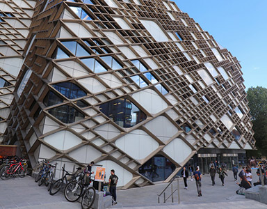 Exterior shot of The Diamond showing students, bikes and blue sky