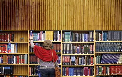 Researcher reaching for a book in the library