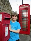 Boy standing next to letter box