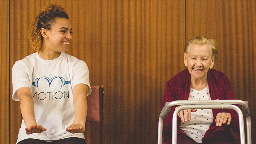 Student helps elderly person exercise for Motion: Enactus project