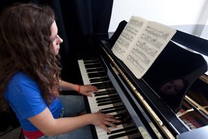 BMus with foundation year. Female student playing a song on the piano.
