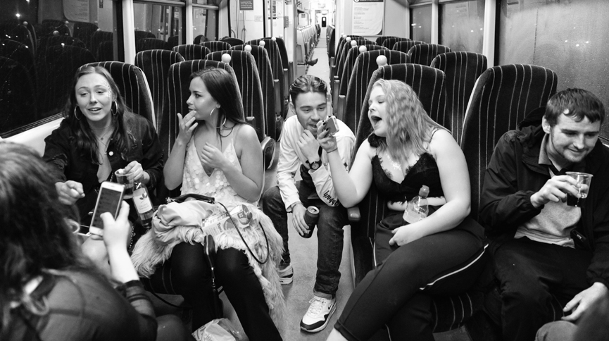 A group of friends enjoying a drink and a laugh in a train carriage