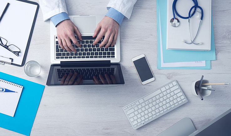 Photo showing birds eye view of doctor at desk with laptop