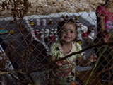 A child looking through a wired fence