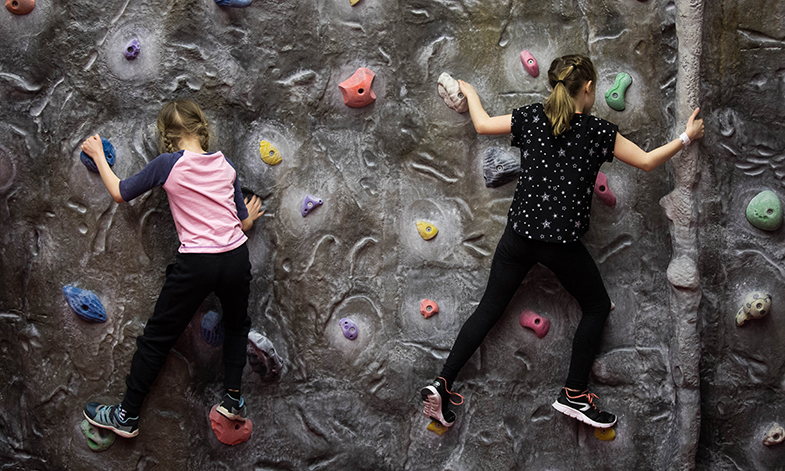 Two children climbing on a bouldering wall