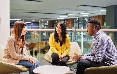 Three students sitting and chatting in the Students' Union.
