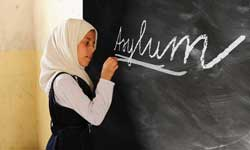 Girl writing 'asylum' on a blackboard