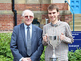 Photo of Graham Battersby presenting mooting cup to student