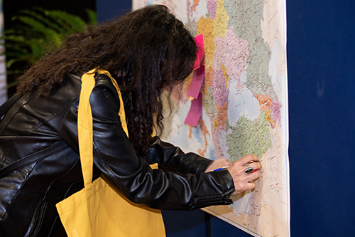 Colleague placing a note on world map