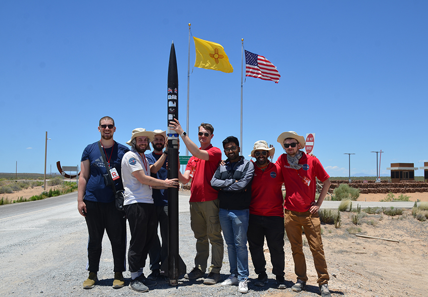 Students from the SunrIde team posing with their rocket