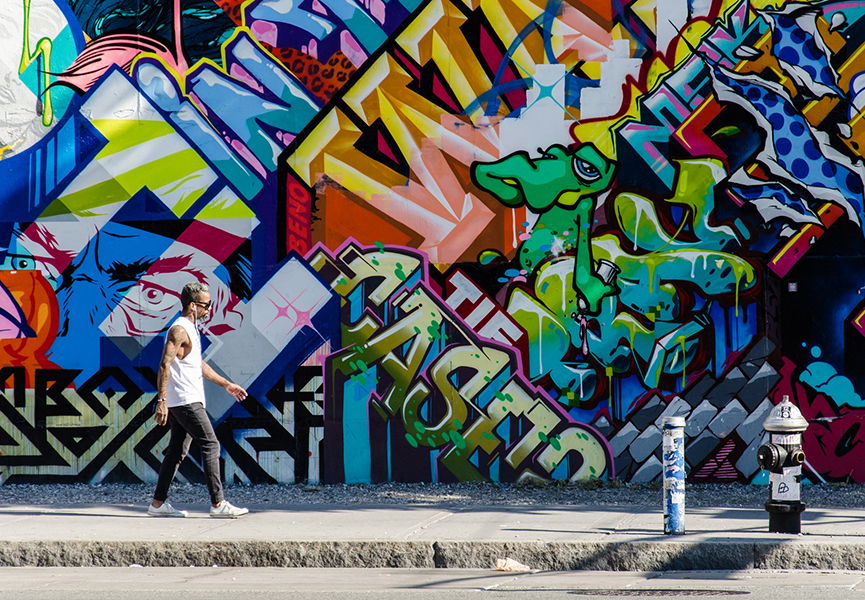 A young male hispter walking in front of a wall of graffiti in Brooklyn, New York