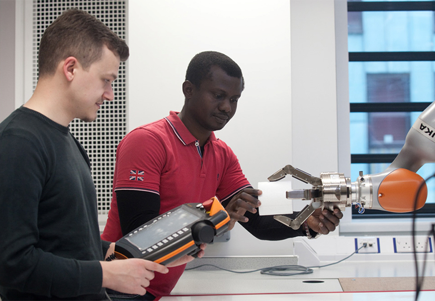 Two apprentices programming a robotic arm