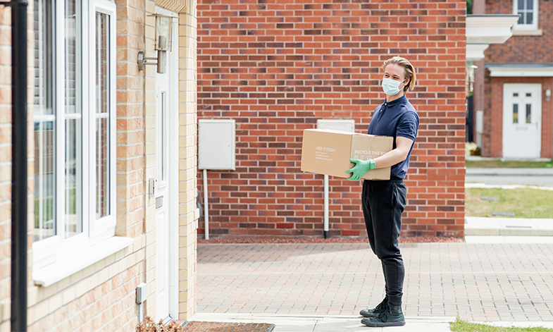 A young man stands outside a residence with a covid-safe delivery, he is wearing a mask.