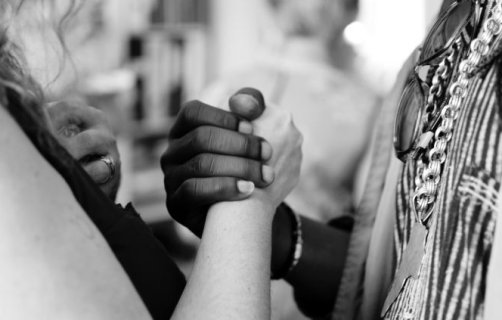 Black and white photo of two people joining hands