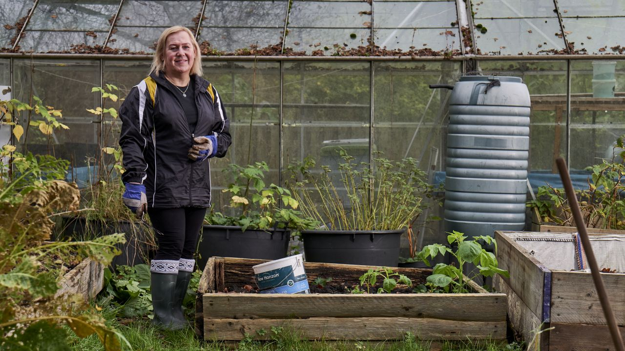 A woman is stood in an allotment next to a raised bed. There is a greenhouse in the background and several tubs of plants growing