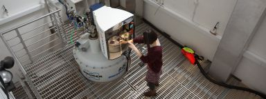 A researcher loads a sample into the 800 MHz spectrometer