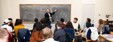 A lecturer stood at the front of a seminar by a blackboard