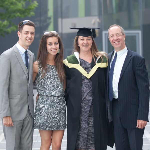 Mature student poses for camera with family at graduation