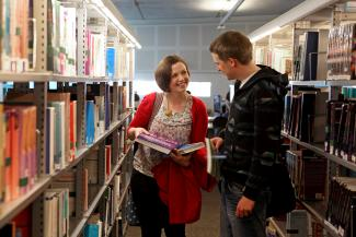 Image of two postgraduate students from the Department of Human Communication Sciences in library