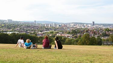 Students sat in park overlooking the Sheffield skyline