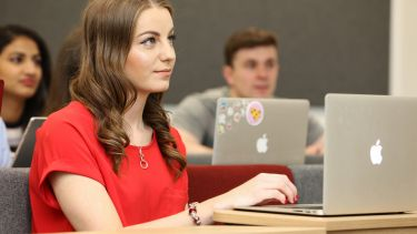 Girl in red in lecture with laptop computer