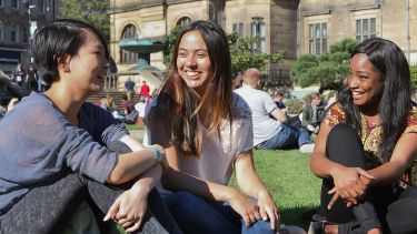 Students sitting in Peace Gardens by Town Hall