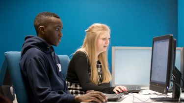 Image of two postgraduate law students on computer with blue background