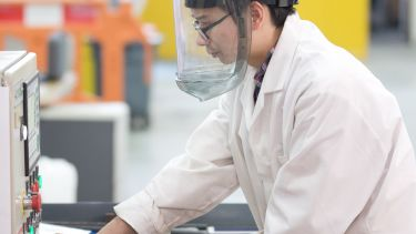 Image of postgraduate materials science and engineering student using equipment with mask