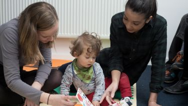 Postgraduate psychology students Evie Smith and Ciara Kelly reading with child