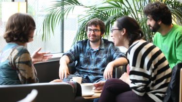 Postgraduate philosophy students sitting around coffee table
