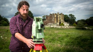 Medieval archaeology postgraduate with castle in the background