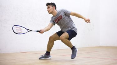 A student playing squash in the university gym