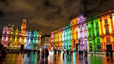 Buildings in Lyon lit with rainbow lighting